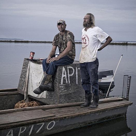 Roscoe Rotella, 34, (left) and Terry Nowling, 50, relax on their oyster boat after a day of oystering on the Apalachicola Bay. Both men have been catching oysters for their entire lives. (Photo by Jeremiah Stanley)