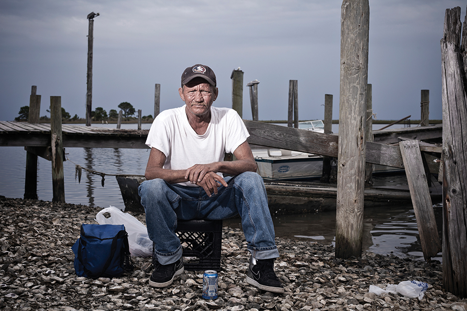 Carl Sanders, 52, sits on the shore of the Apalachicola Bay after a day of catching oysters. He has been an oysterman his entire life. (Photo by Jeremiah Stanley)