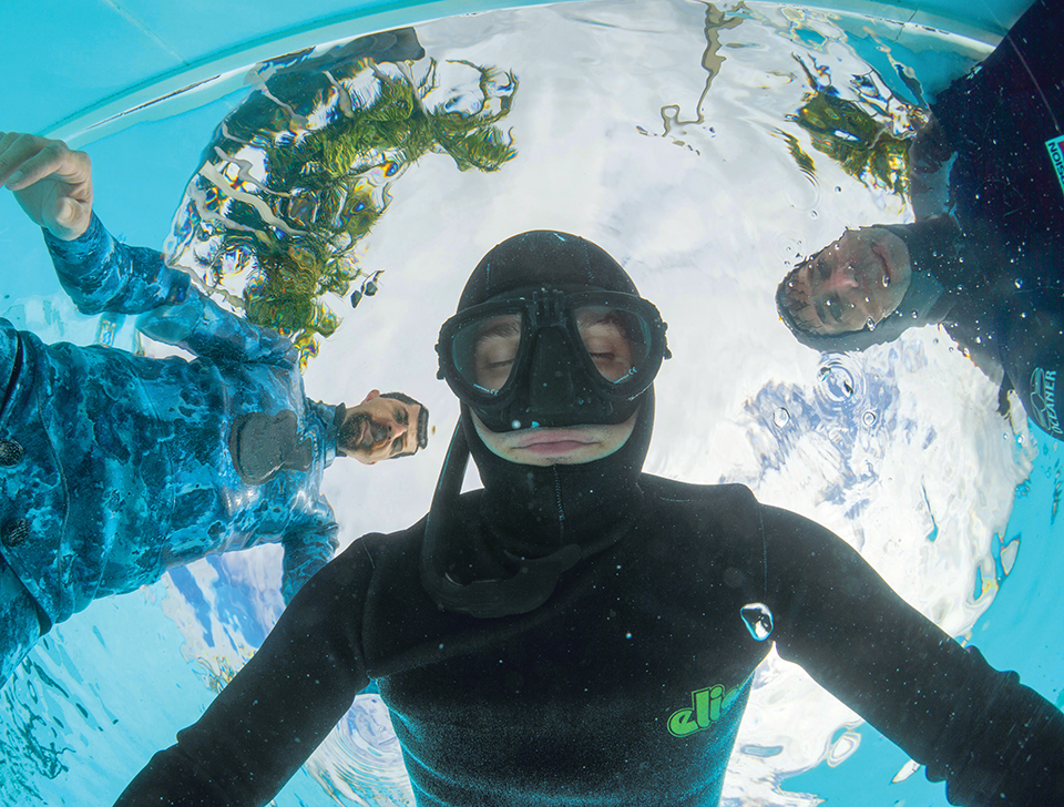 Freedivers practice holding their breath while lying facedown in a pool. Photograph by Immersion Freediving