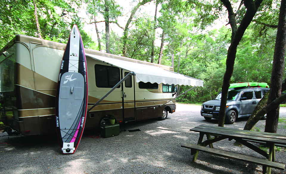 The author's camper and paddleboard, essential items for outdoor Florida adventures; Photograph by Kevin Mims