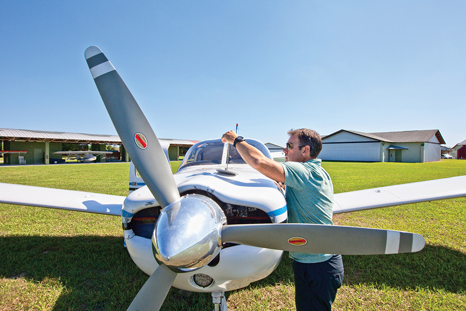 Jamie Clifford checks the oil level in his plane before take off. Photograph by Jeremiah Stanley