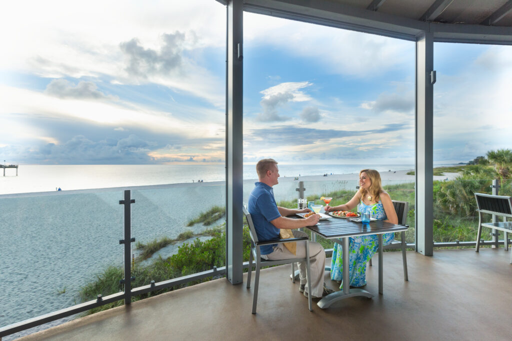 Two diners, a man and woman, enjoy a beachfront meal in Savor Sarasota.