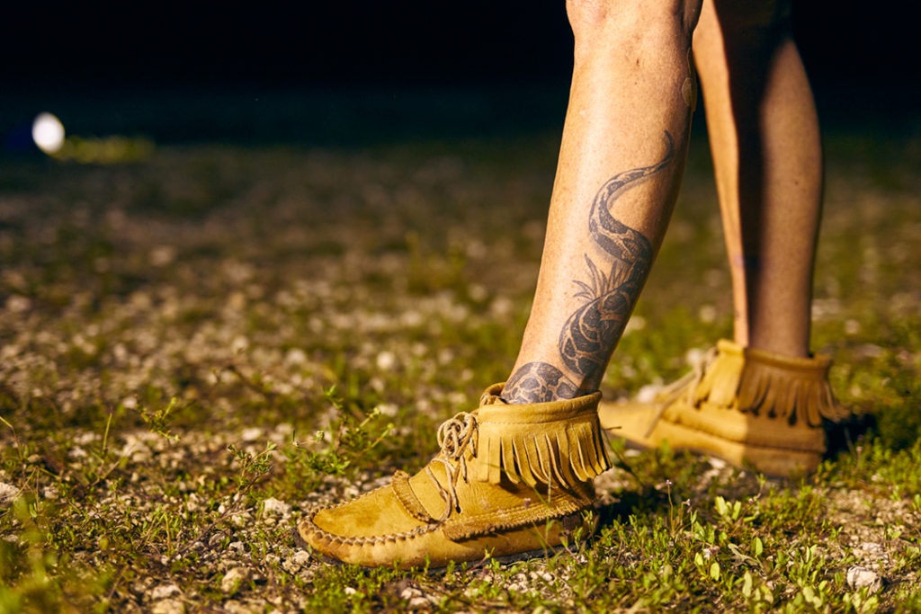 Anne Gorden-Vega's legs. A python tattoo is on her calf, and she wears moccasins.