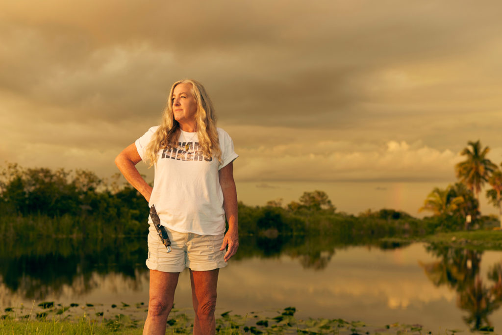 Anne Gorden-Vega stands in a powerful stance against a swampy backdrop. It looks to be around sunset, as the picture has a glow. She wears khaki shorts and a white shirt. A sheathed knife is on her waist.