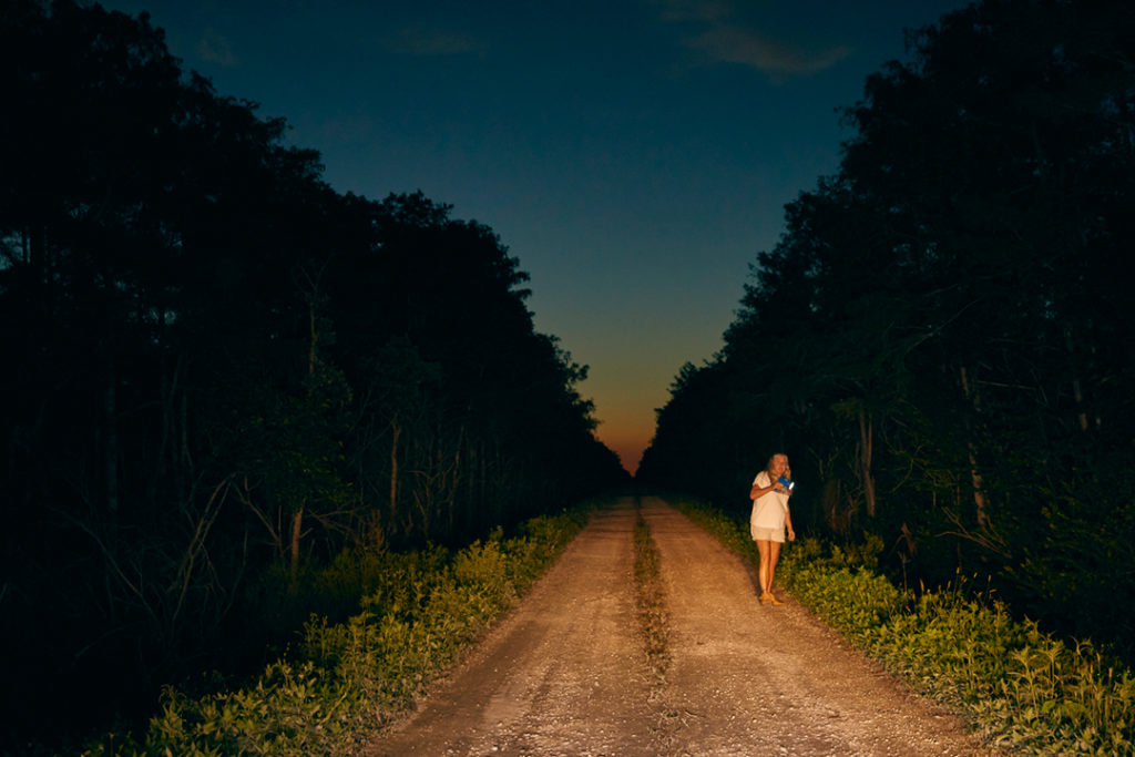 A dusk photo. Anne Gorden-Vega is visible, as the front of the picture is illuminated. Trees line each side of the dirt path Gorden-Vega stands on looking for pythons.