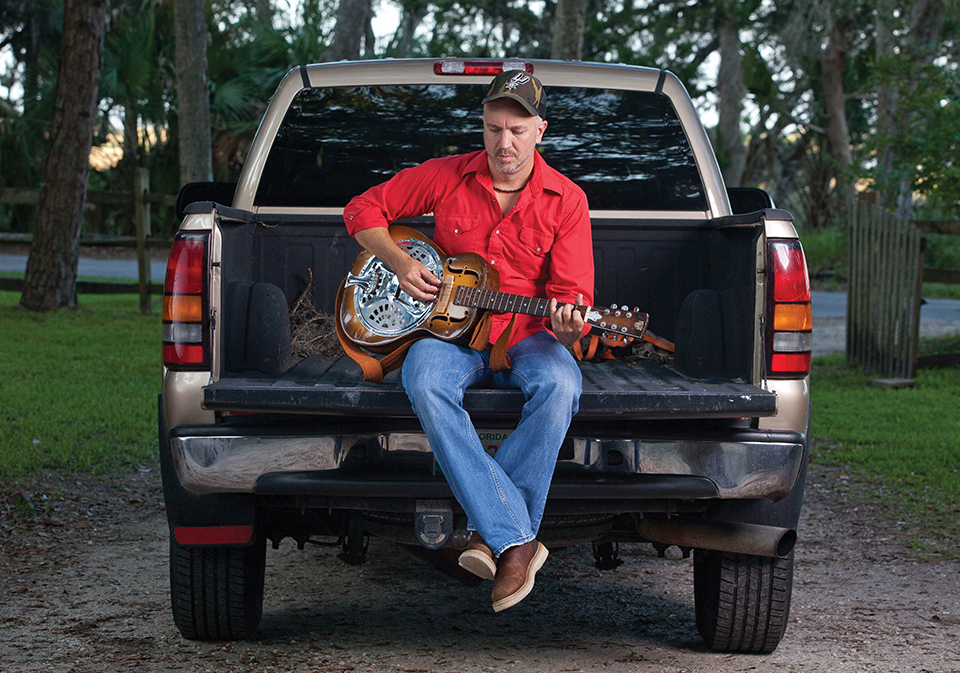Grey strums a Dobro guitar while sitting on the tailgate of his truck at home in North Florida. Photography by Jeremiah Stanley