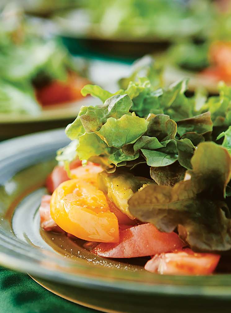 Red and yellow tomatoes, covered with leafy lettuce; Photography by Hannah Glogower