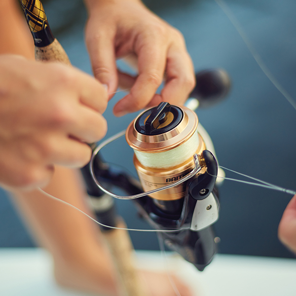 Spooling a spinning reel; Photography by Mary Beth Koeth