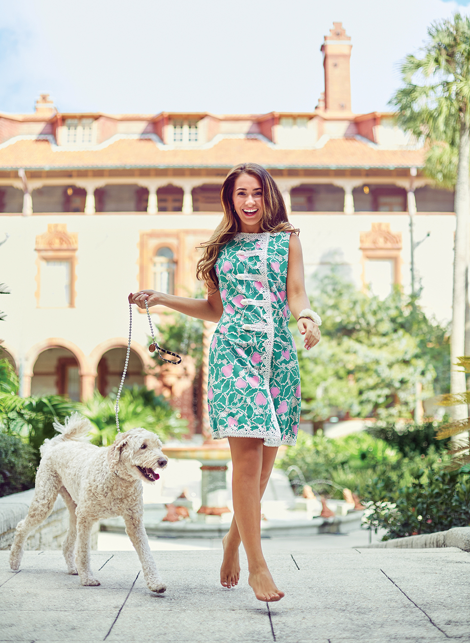 Floridian Eve Gay wears a vintage Lilly Pulitzer shift while playing with her labradoodle Jobi at Flagler College's historic Ponce de León Hall, in St. Augustine. Photography by Mary Beth Koeth