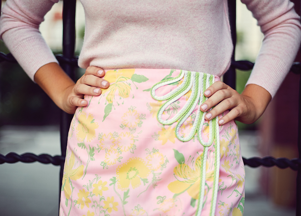 A close-up of Eve in a vintage Lilly floral skirt. There is a pink background, yellow florals and white and green piping. She has her hands on her hips and wears a pink sweater. The photo only features her torso, not her head or legs.
