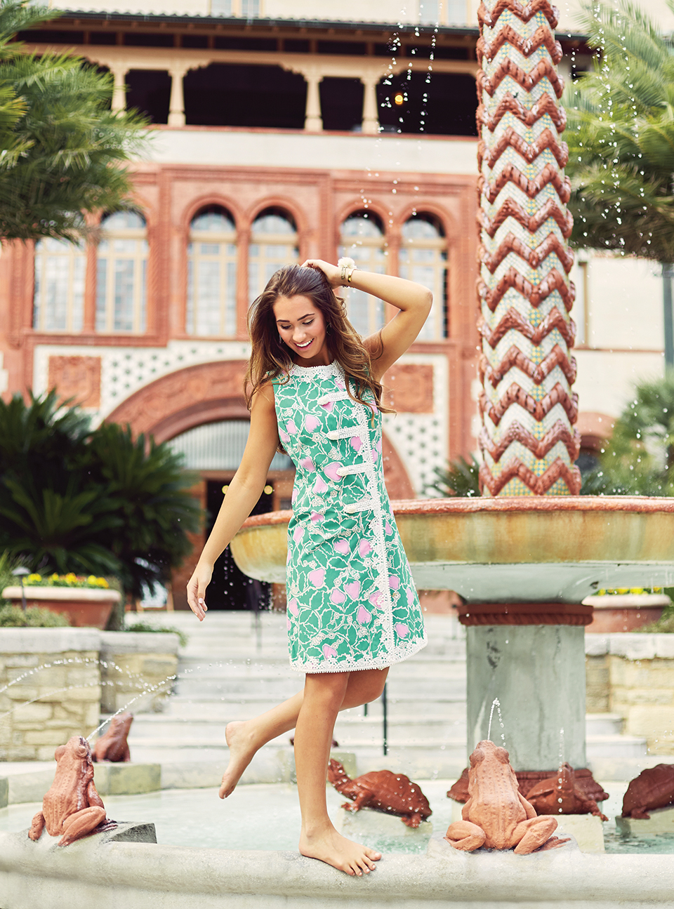 Model Eve Gay wear a vintage green and pink Lilly dress with white lace details. The photo is taken at Flager College. Eve stands, almost like a flamingo, on a fountain's ledge and runs a finger through her hair. The fountain features turtles and frogs spouting water.