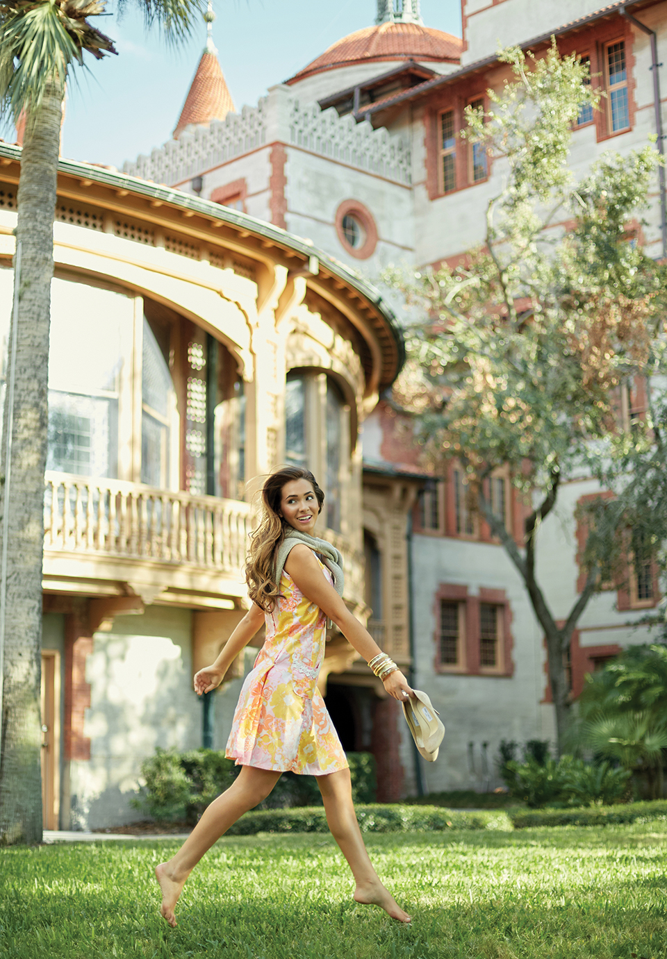 Eve wears a orange, pink and yellow floral Lilly dress with a sweater tied around her shoulders. She holds tan pumps as she struts across the grass with Flagler College's historic architecture in the background.