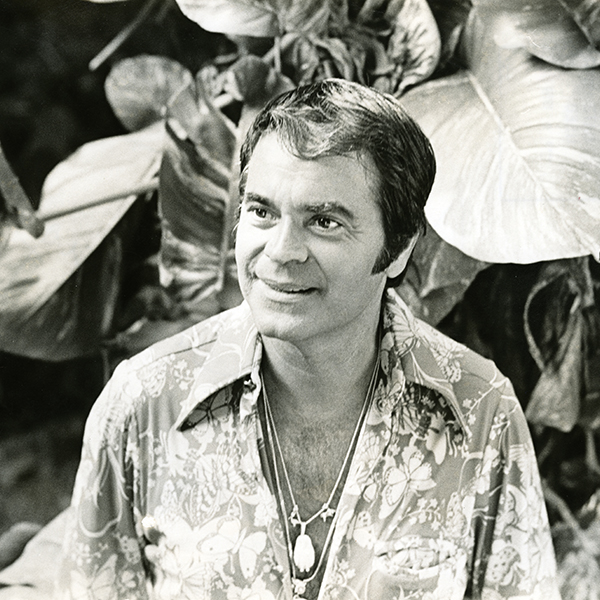 A black and white photo of Jim Russell. He wear a Hawaiian shirt that seems to be unbuttoned. He wears necklaces that rest on his chest.