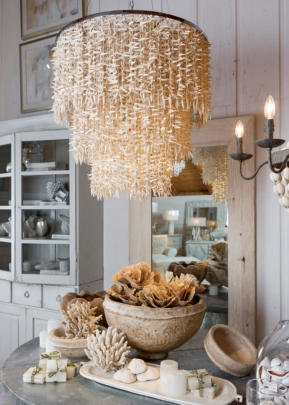 A white-washed space is punctuated by a shell chandelier and mollusk treasures. Photography by Duh for Home and Garden