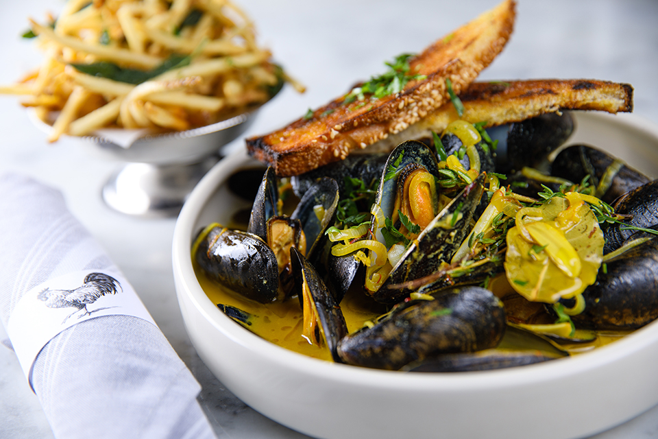The menu highlights classic dishes, such as moules frites and tartare de bouef. Photography by Michael Caronchi