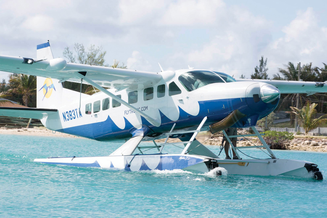 A blue and white seaplane that brings tourists to the Bahamas floats on the water. Numbers and letters on the plane read N383TA. It also says flytouwrist.com.