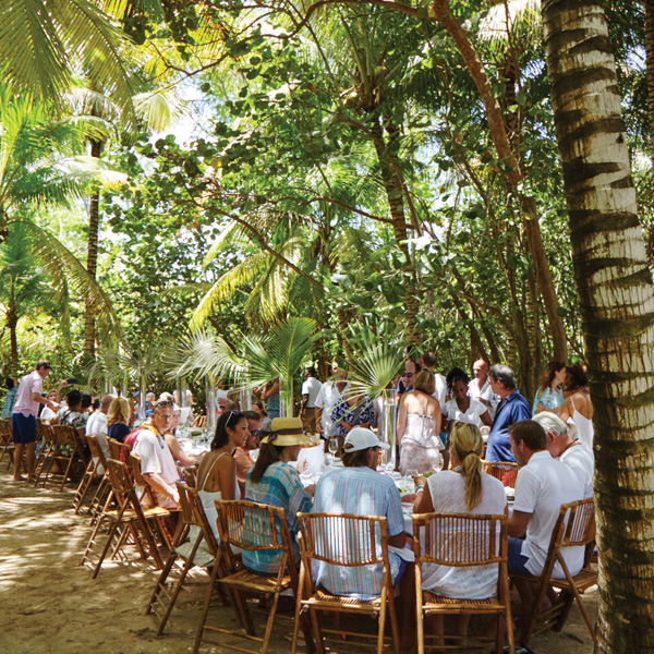 A large group gathers for a meal in the sand under the shade of tropical foliage.