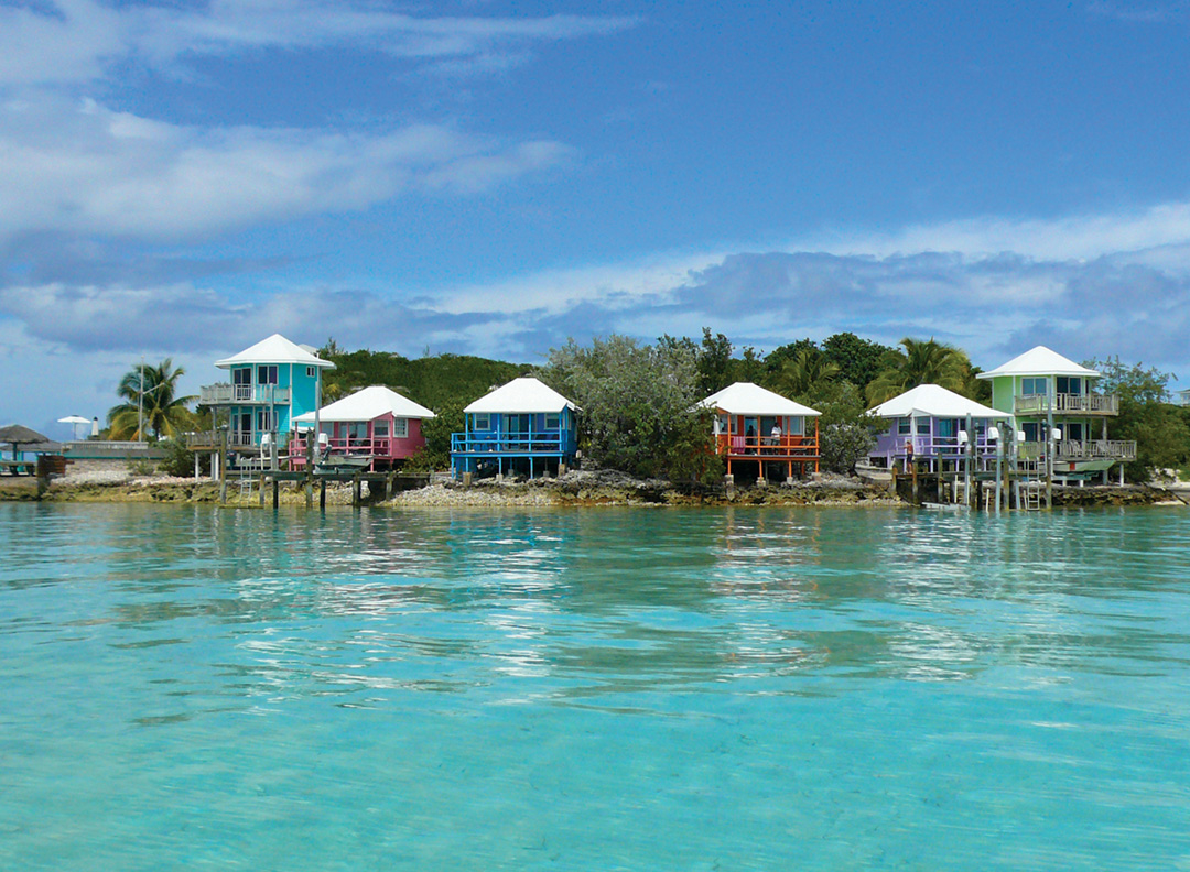 Colorful cottages on stilts are nestled in the shoreline and reflected into the rippling water.