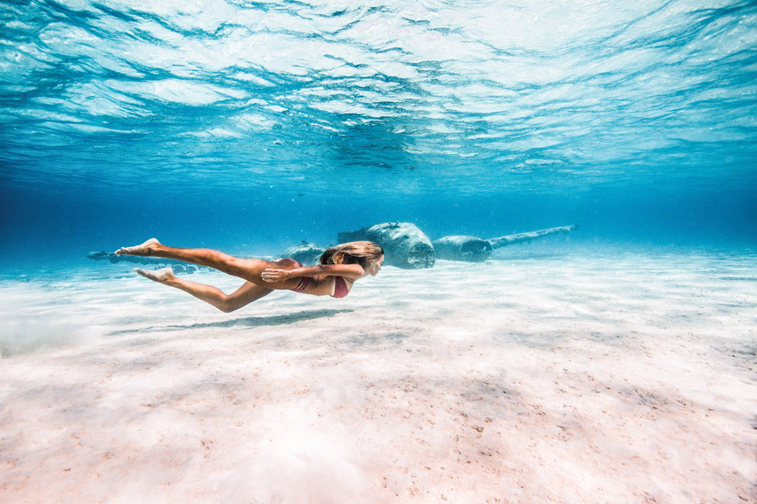 A woman snorkels in the Bahamas in front of a sunken airplane wreck in this underwater photo. Dark shapes are hard to make out but are the plane. The water is clear.