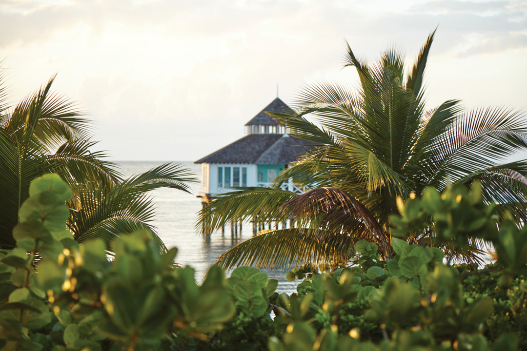 A home rests on stilts above the water. In the foreground, tropical foliage frames the home in the background.