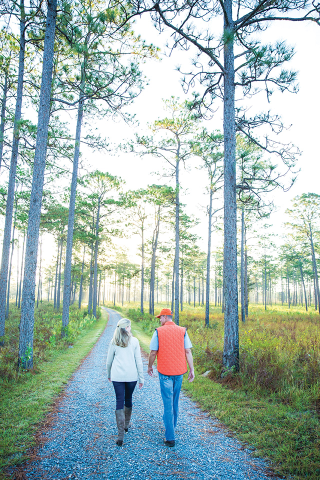 Slade Sykes and a Baker family member walk through the longleaf pine forest on a recent fall morning