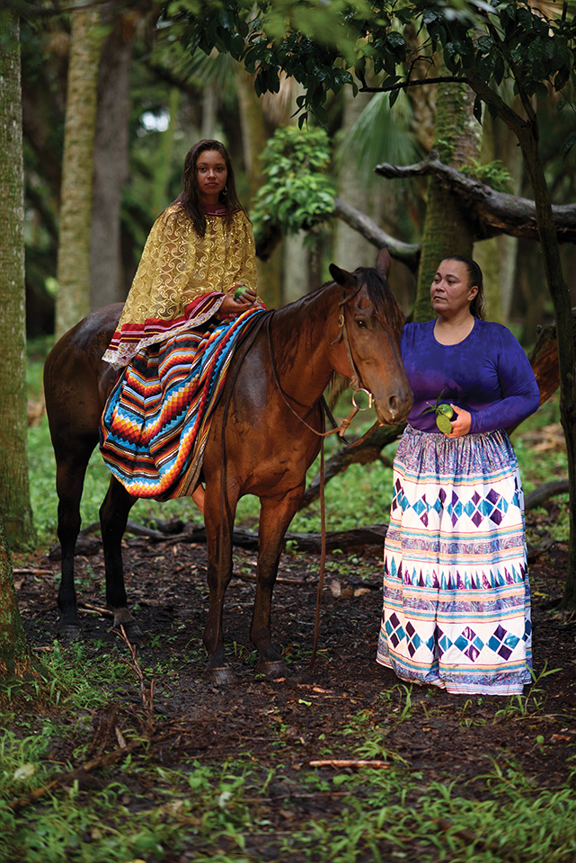 Wearing traditional Seminole dresses, Morgan and her mother Louvella Yates pick fruits on the Brighton Reservation