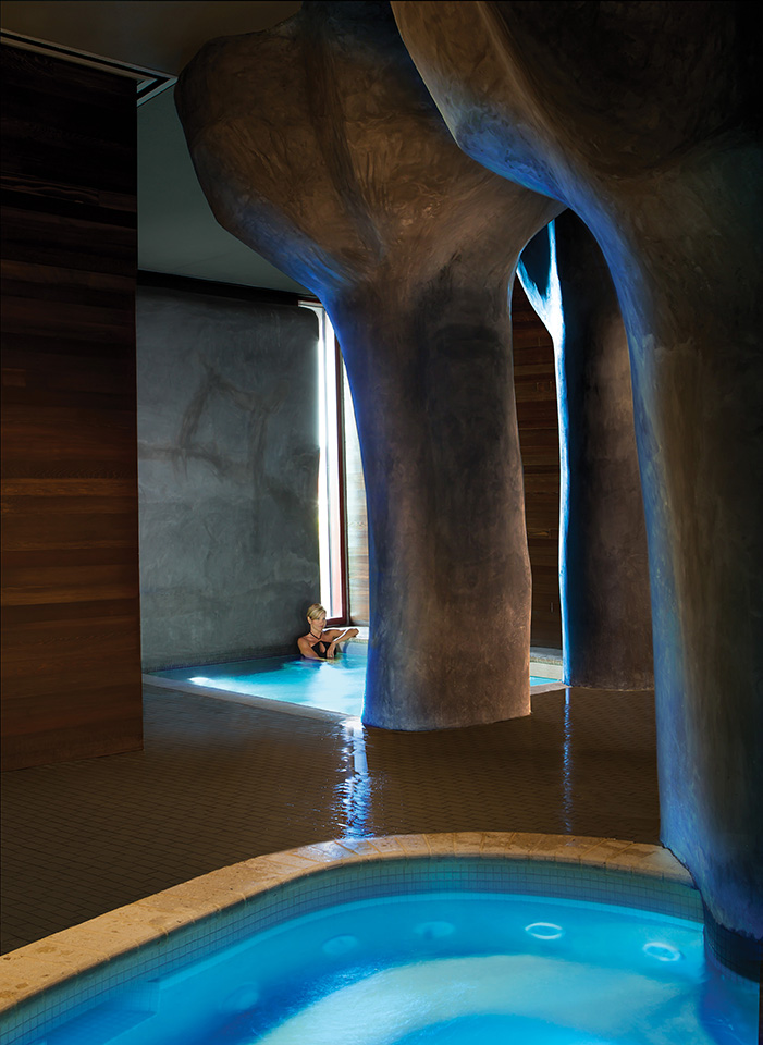 "Inside the spa, ""petrified tree"" columns surround the seven pools."