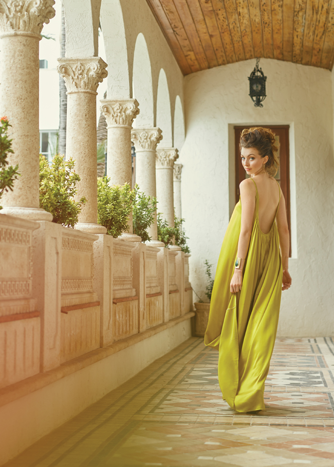 Krystoff wears a chartreuse dress and an updo as she looks over her shoulder while walking the the boutique hotel where Gianna Versace once resided.