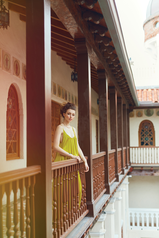 Krystoff in the chartreuse dress is on a balcony overlooking the courtyard.