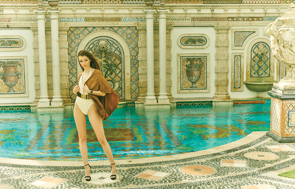 Krystoff poses in front of the opulent pool featuring columns and mosaics.