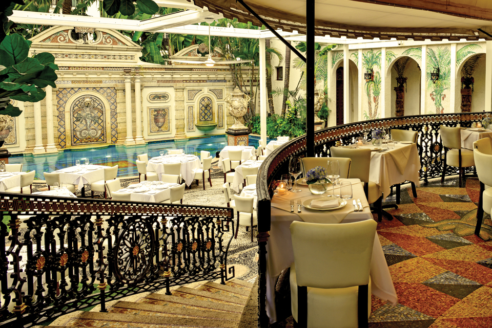 The Versace dining room overlooks the pool. Tables are set up ready for guests.