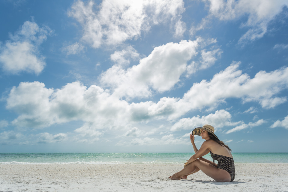 Woman in a hat sits on the beach surrounded by blue skies.