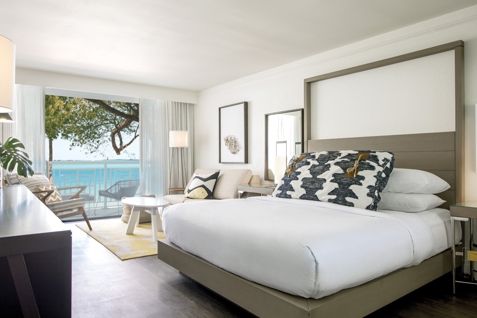 Image of a remodeled hotel room: large plush bed, chairs, and a balcony that overlooks the ocean.
