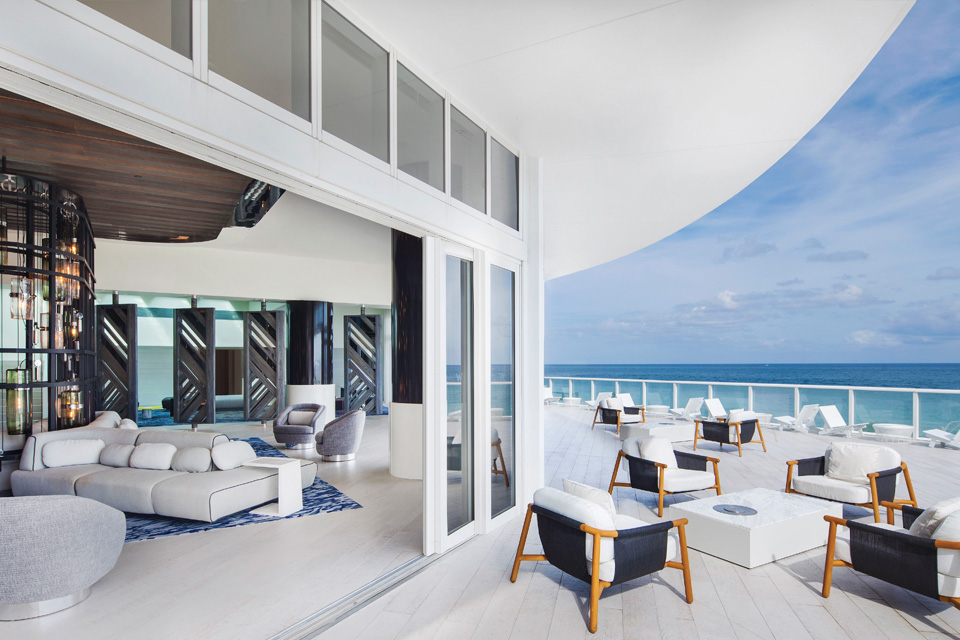 Image of a lounge at a modern hotel that overlooks the ocean.