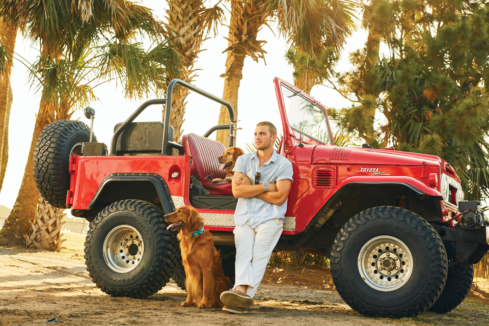 Cover model Noah Sanford with retrievers Piper and Star posing with a vintage red FJ cruiser.