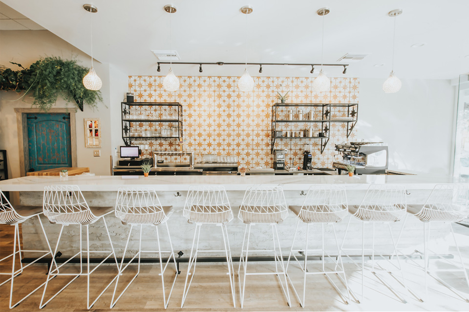 Image of the bar counter at Proper & Wild, a clean look with lots of white furniture and yellow and white tiles.