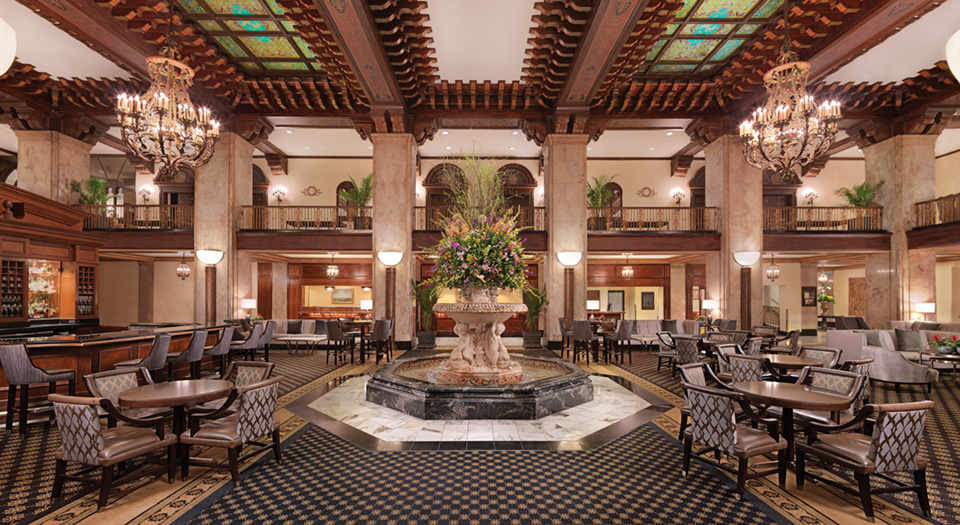 Image of a Italian Villa inspired hotel lobby filled with chairs and a fountain.