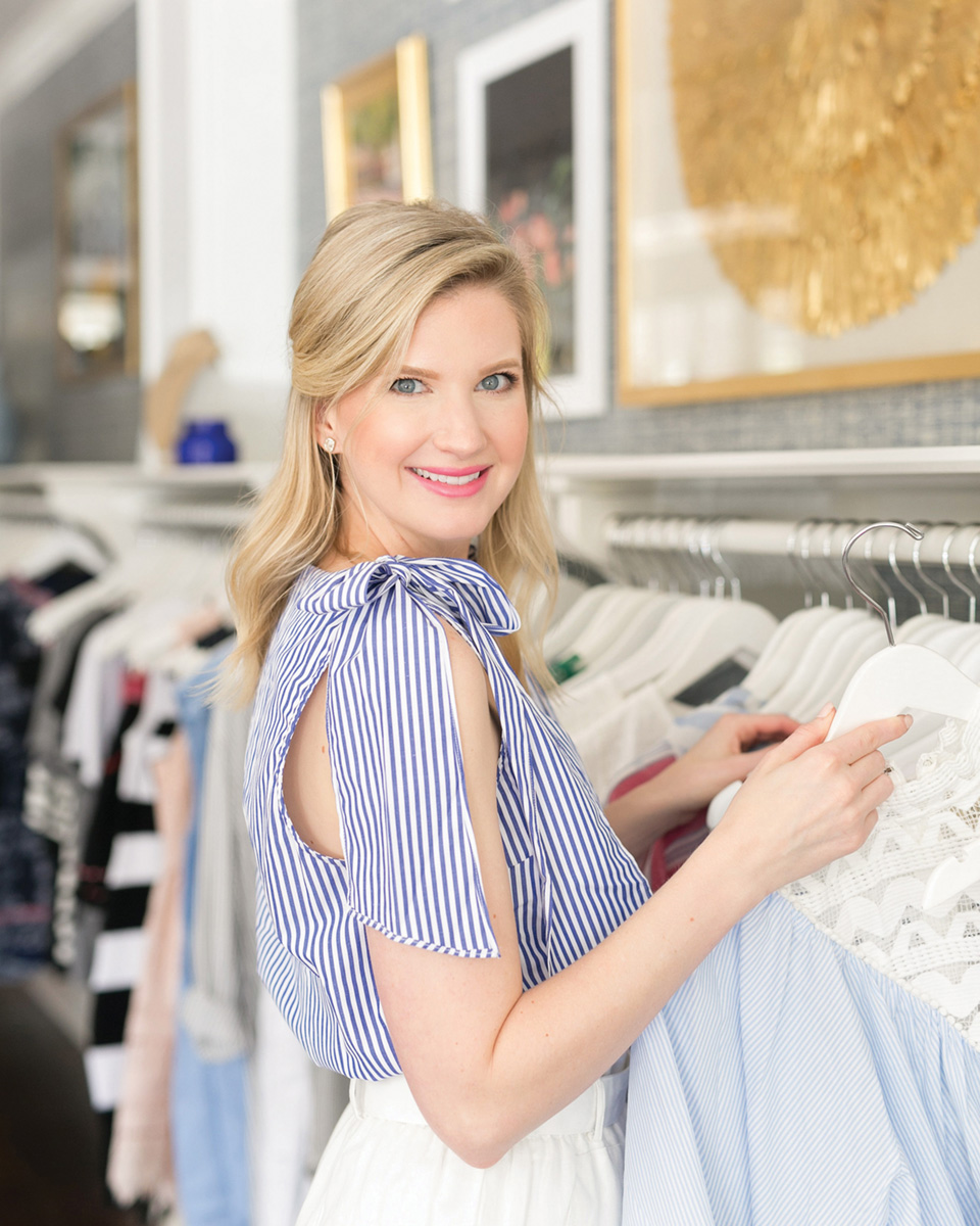 Image of Ashley Brooke in front of a clothing rack.