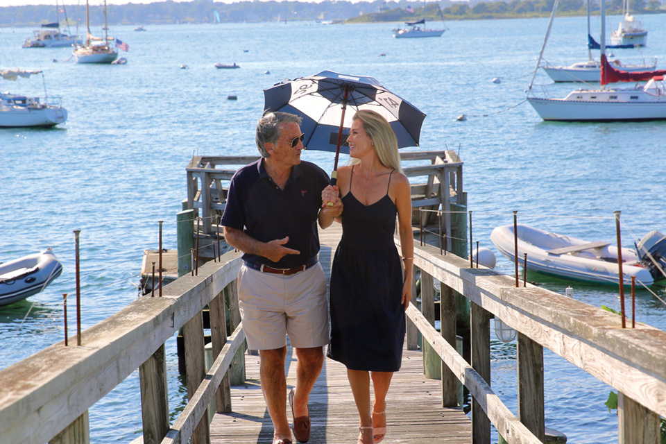 A couple walks on a dock using the Bimini-me sun shade. They appear in conversation and are smiling.