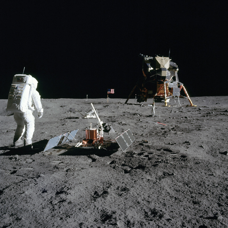 Image from the surface of the moon, 1969. Moon Rover and Surface craft pictured along side a single astronaut and American flag.