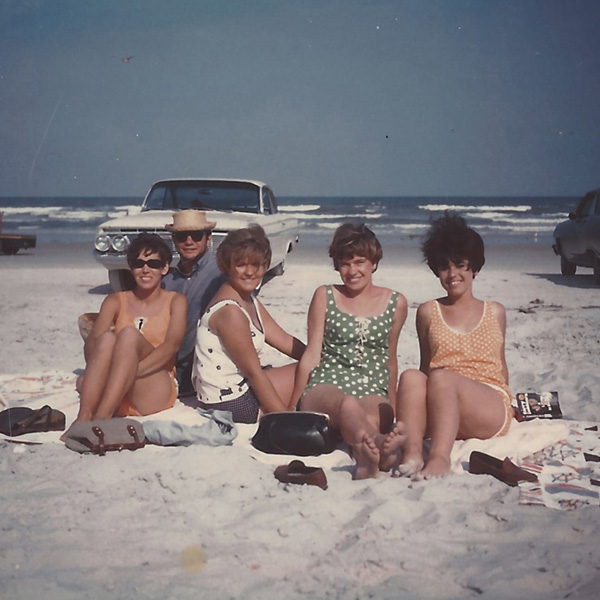 Group of people on a beach from a vintage photograph, cars and soft waves in the background.