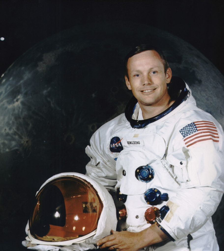 Photo of Neil Armstrong in his astronaut gear sitting in front of a picture of the moon.