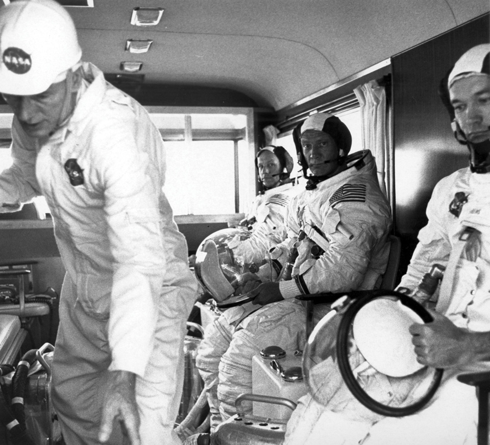 Black and white image of 3 Astronauts on the way to the launch pad and a service member.