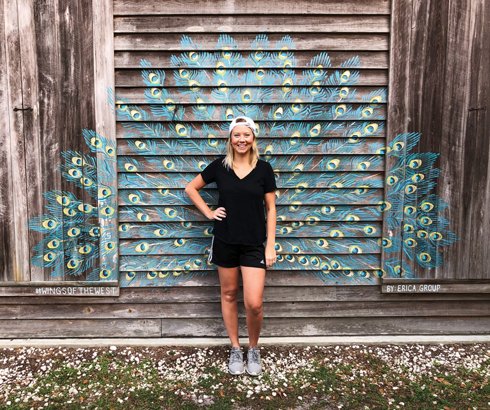 Erica Group posing in front of one of her peacock murals. The mural is painted onto a rustic wood building.