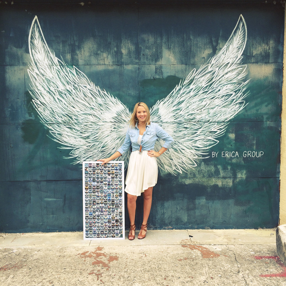 Picture of Erica Group in front of her iconic white wing murals. The mural has two large white angel like wings. The artist is also holding a collage of her many wings.
