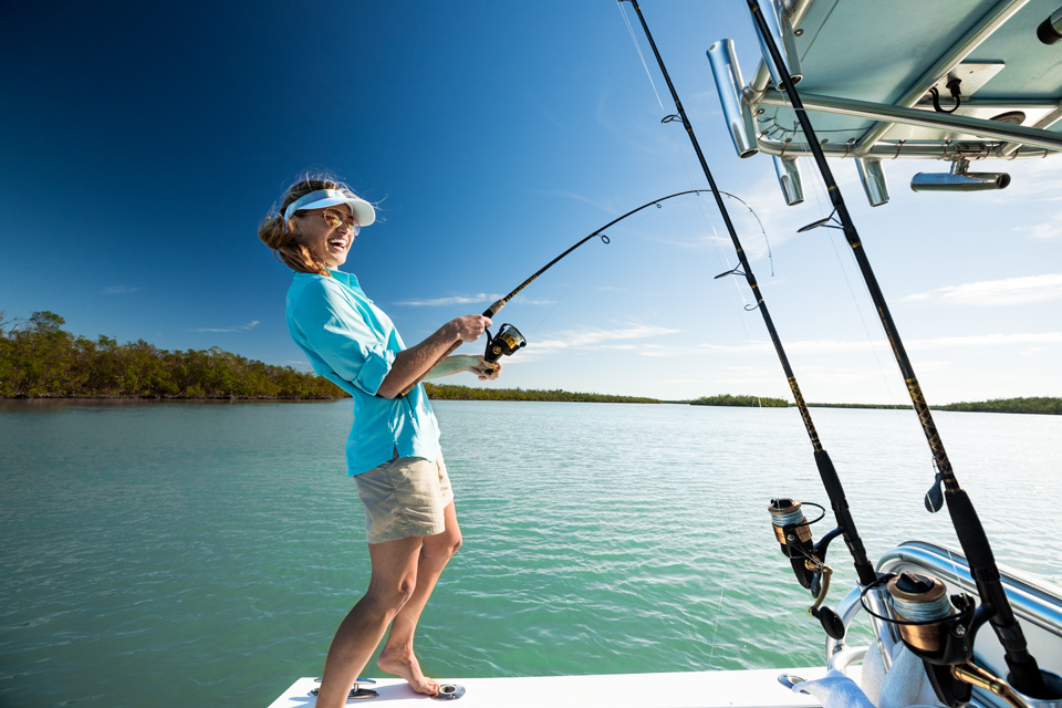 Smiling woman catching a fish on a boat thats located in the Everglades.