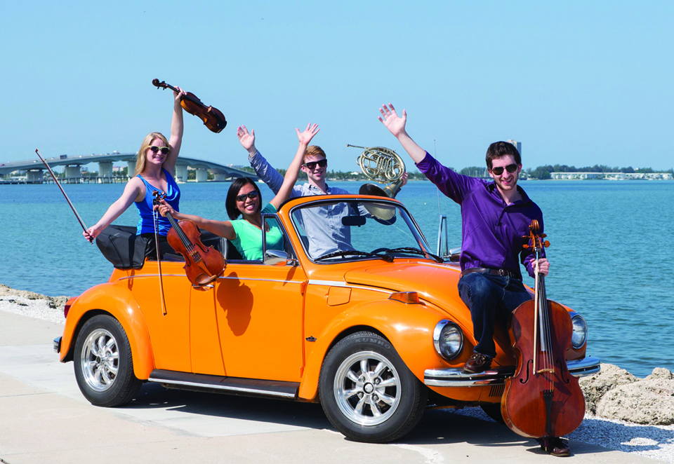 Group of smiling young people holding instruments posing in and around a vintage goldenrod yellow Volkswagen Beetle. Sarasota's waterways and a bridge are pictures in the background.