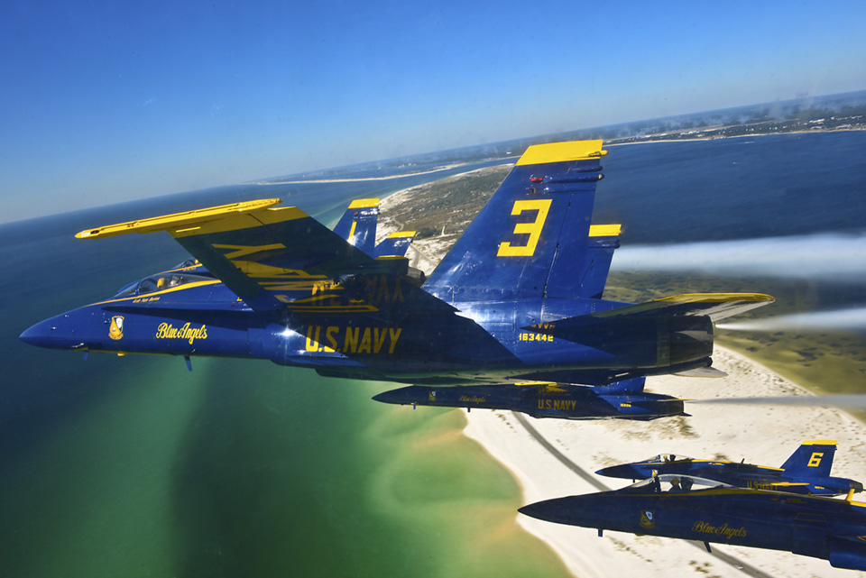 Close-up shot of The Blue Angels Demonstration Squadron flying in a delta formation over Pensacola Beach.