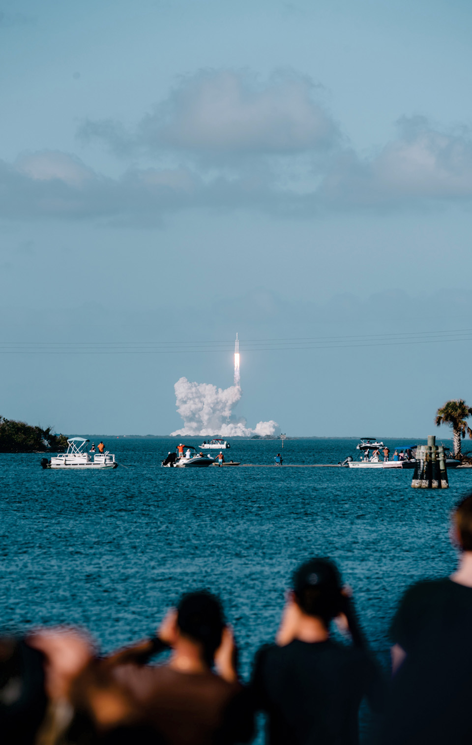 Revelers watch as a rocket embarks on a 200-mile journey up. People are watching in the foreground over the water which is dotted with boats also onlooking the rocket in the background.
