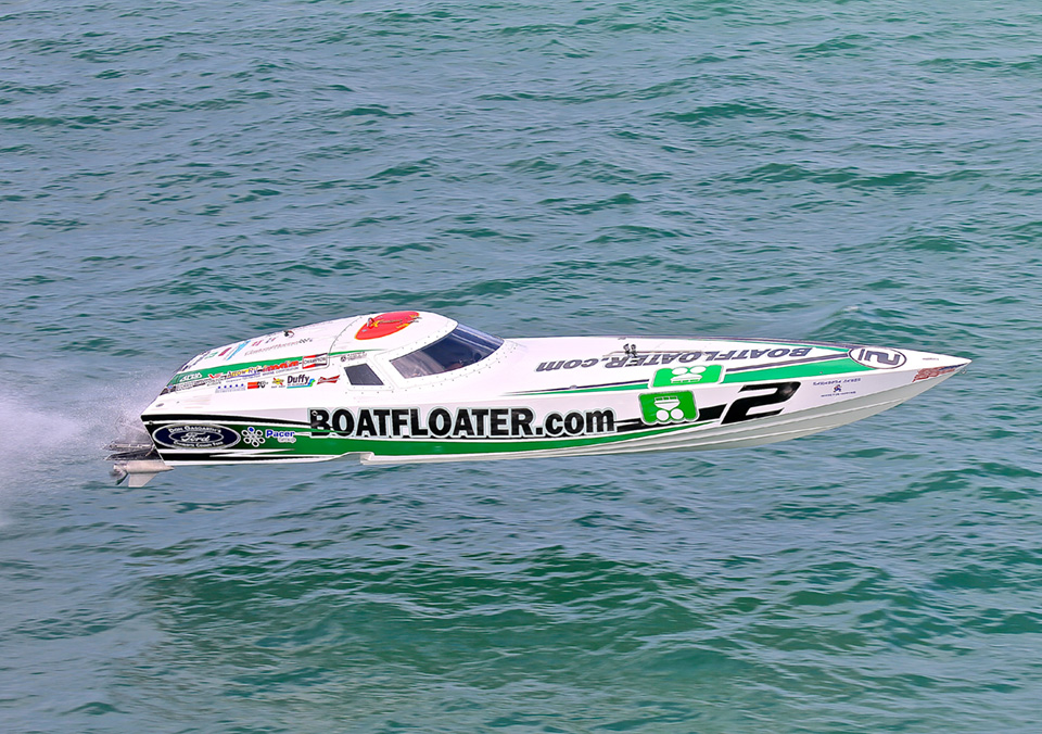 Appearing to be flying, a green sponsored powerboat racer speeds along the water.